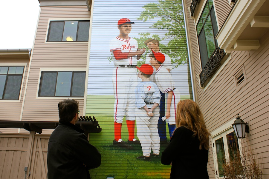 Artist Andy Eccleshall (left), and curator Terese Clark look up at a mural of Seattle baseball legend Edo Vanni at Aegis of Queen Anne at Rodgers Park. Photo by Joe Veyera