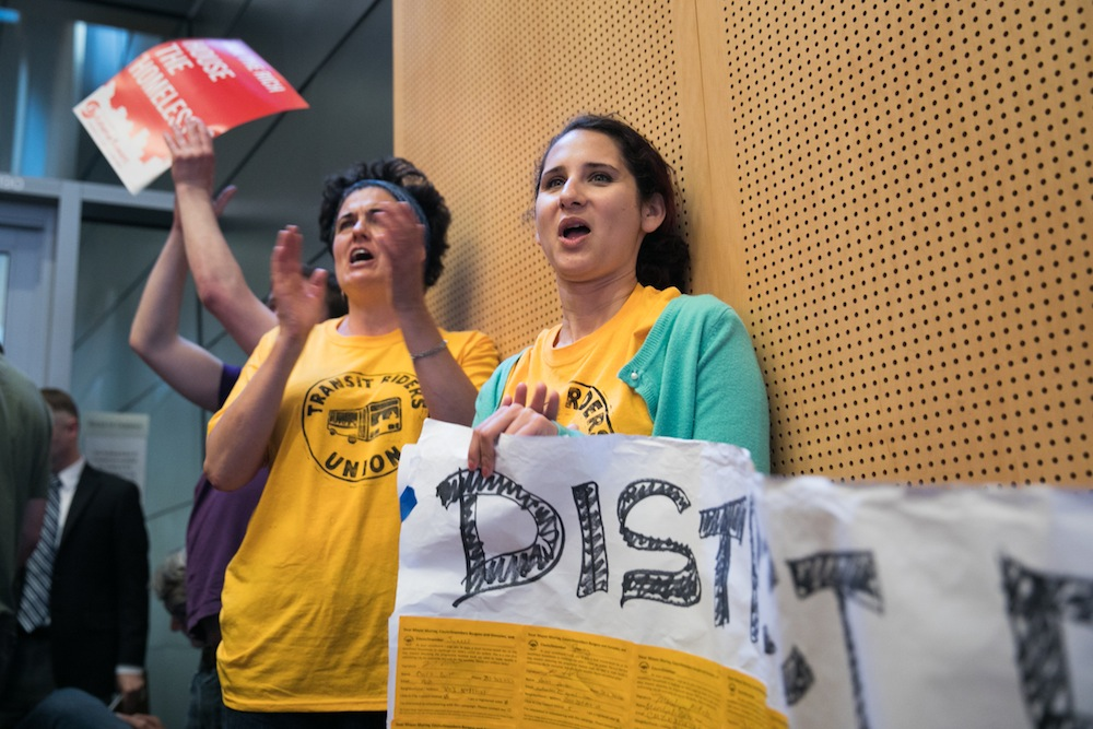 Gabrielle Olivera, right, and Holly Eckert cheer as supporters of an income tax on Seattle's wealthiest residents testify at a public hearing before the City Council on Wednesday, June 14. Photo by Lizz Giordano