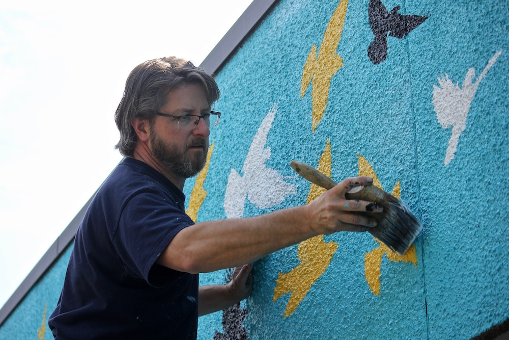 Artist Andy Eccleshall works on the new mural in Magnolia Village last week, ahead of its Sept. 8 dedication and celebration event. Photo by Joe Veyera