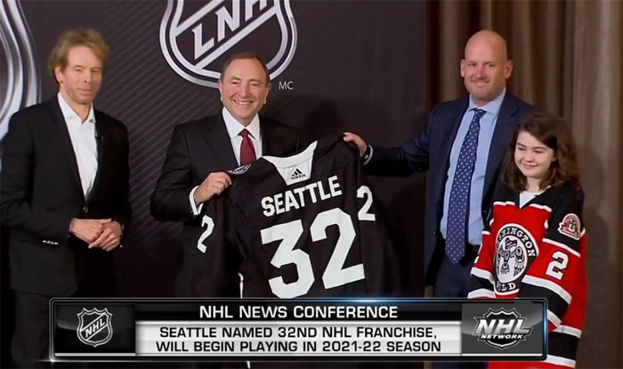 Image from NHL: NHL Commissioner Gary Bettman, center, accepts a Seattle hockey jersey from Seattle Hockey Partners Group co-owners Jerry Bruckheimer and David Wright.