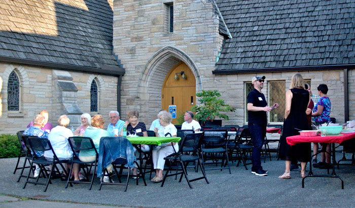 Magnolia residents sit outside of United Church of Christ. Rex McDowell, who set up the National Night Out event at the church, said he helps out because,  'it's an excuse to get out of work early and is a great chance to meet neighbors.'