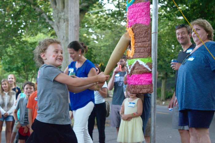 A girl at the Fifth Avenue West and West Halladay Street block party takes a whack at a piñata.