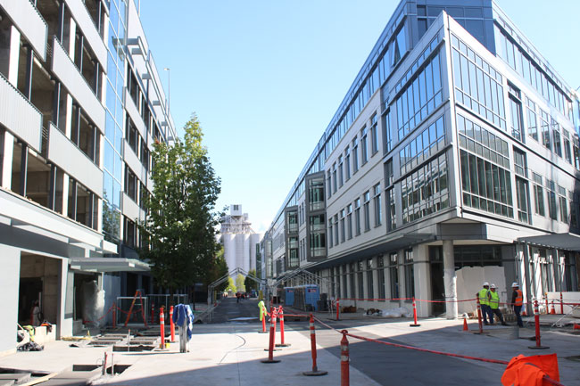 A pedestrian plaza runs between a parking garage and repurposed Amgen buildings in Interbay.