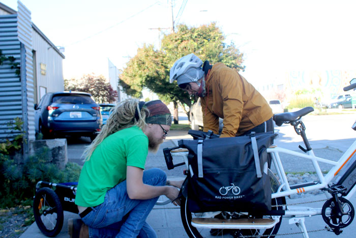 Jesse Erickson and Leah Chung hitch a trailer to a Rad Power Bike before Chung makes deliveries on Thursday, Oct. 10.
